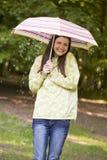 Frau draußen im Regen mit dem Regenschirmlächeln Stockfotografie