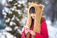 Frau draußen mit Mobiltelefon in der Winterzeit Stockfotos