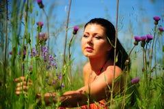 Frau draußen unter wilden Blumen Stockfotos