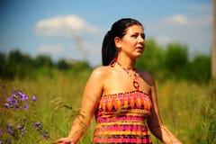 Frau draußen unter wilden Blumen Lizenzfreies Stockfoto