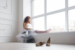 Frau durch das Fenster stockbild