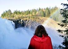 Frau durch einen schäumenden Wasserfall Stockfoto