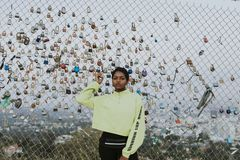 Frau durch einen Zaun mit Vorhängeschlössern im LA stockbilder