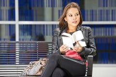 Frau, ein Buch lesend, das Blickkontakt aufnimmt Lizenzfreies Stockfoto