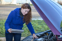 Frau ein Treiber mit der Berührungsfläche, die gebrochenes Auto repariert Stockfotografie