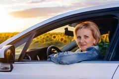 Frau in einem Auto, das Kamera durch Fenster betrachtet Stockfotografie