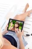 Frau in einem Badeanzug, der auf einem Wagenaufenthaltsraum mit einer Tablette a liegt lizenzfreie stockbilder