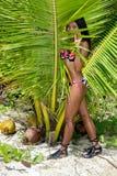 Frau in einem Badeanzug, der in den Blättern sich versteckt Stockfoto