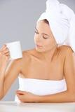 Frau an einem Badekurort, der einen Becher Kaffee betrachtet Stockfoto