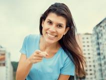 Frau in einem blauen Hemd zeigend auf Kamera im kühlen Kinoblick Lizenzfreies Stockbild