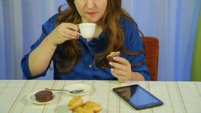Frau in einem Caf? an einem trinkenden Kaffee der Tabelle mit Nachtisch und dem Ablesen der Nachrichten auf der Tablette stock footage