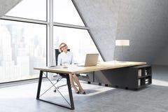 Frau in einem CEO-Büro mit dreieckigem Fenster Lizenzfreies Stockfoto