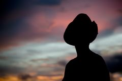 Frau in einem Cowboyhut silhouettiert gegen einen Sonnenuntergang Stockbild