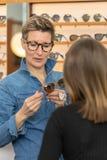 Frau in einem Eyewearspeicher stockbild