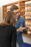 Frau in einem Eyewearspeicher lizenzfreie stockfotos