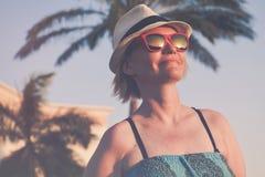 Frau an einem Feiertag mit rosa Sonnenbrille und weißen der Hutentspannung im Freien lizenzfreie stockfotos