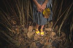 Frau in einem gestreiften Rock und in gelben Sandalen, die im dunklen tropischen Wald stehen und ein großes Blatt halten lizenzfreie stockfotos