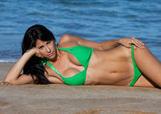 Frau in einem grünen Bikini auf dem Sand Stockbilder