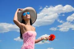 Frau in einem großen gestreiften Hut mit der Mohnblume blüht Stockfotografie