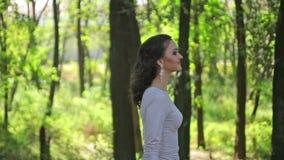 Frau in einem hellen Kleid gehend in einen Wald stock video