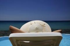 Frau in einem Hut, der über dem Meer stillsteht Lizenzfreie Stockfotografie