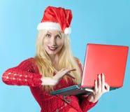Frau in einem Hut des neuen Jahres mit rotem Laptop Lizenzfreie Stockfotografie