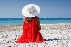 Frau in einem Hut durch das Meer lizenzfreies stockbild