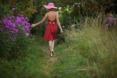 Frau in einem Hut geht unter den Blumen Stockfotografie