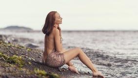 Frau in einem Kleid auf einem Strand Lizenzfreies Stockbild