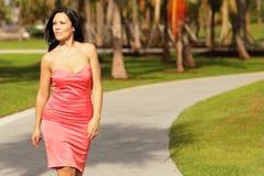 Frau in einem Kleid gehend in den Park lizenzfreie stockfotos