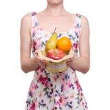 Frau in einem Kleiderblumendruck in der Handkorb-Fruchtapfel-Birnenorange stockbild