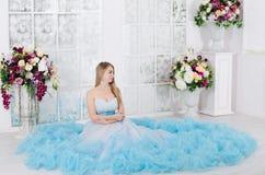 Frau in einem langen blauen Kleid stockbild