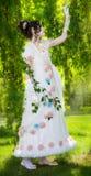 Frau in einem langen, eleganten weißen Brautkleid in einem Park Stockbild