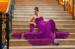Frau in einem langen Kleid, das auf den Treppen liegt Lizenzfreie Stockfotografie