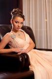 Frau in einem langen Sitzen auf der Couch Stockfotos