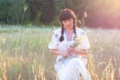 Frau in einem langes Weiß gestickten Hemd erfasst Blumen in einem mea Stockfoto