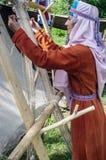 Frau in einem mittelalterlichen Kostüm arbeitet an einem Webstuhl des erfahrenen Arbeiters Lizenzfreie Stockbilder