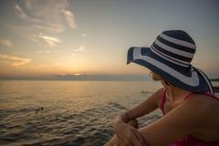 Frau in einem modischen Stroh sunhat, das auf einem Strand heraus schaut O sich entspannt stockbild