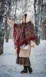Frau in einem Pelzmantel auf einem Weg im Park und im Genießen eines Wintertages stockbilder