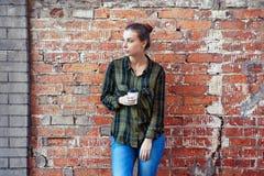 Frau in einem Plaidgrünhemd, das Wegwerfkaffeetasse auf der Hintergrundbacksteinmauer steht Lizenzfreie Stockfotos