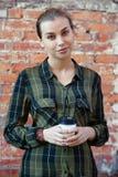 Frau in einem Plaidgrünhemd, das Wegwerfkaffeetasse steht Lizenzfreies Stockfoto
