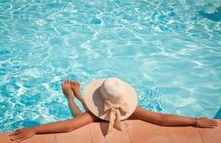Frau in einem Poolhut, der in einem blauen Pool sich entspannt Stockfotos