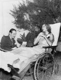 Frau in einem Rollstuhl hörend auf einen Mann, der einen Brief liest (alle dargestellten Personen sind nicht längeres lebendes un stockbild