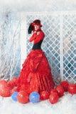 Frau in einem roten antiken Kleid friert unter dem fallenden Schnee ein Stockbilder