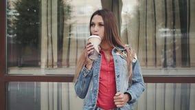 Frau in einem roten Hemd und in einer langen ärmellosen Jackenstellung, zum des Kaffees zu trinken stock footage
