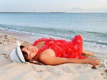Frau in einem roten Kleid und in einem Hut auf dem Strand Lizenzfreie Stockbilder