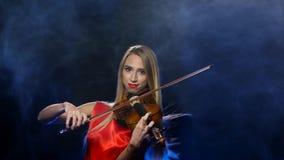 Frau in einem roten Kleid, welches die Geige spielt studio Rauch stock footage