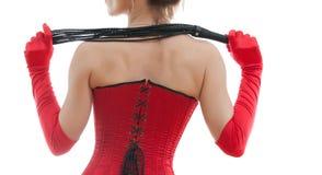 Frau in einem roten Korsett und in einer Peitsche Stockbild