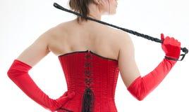 Frau in einem roten Korsett und in einer Peitsche Lizenzfreies Stockbild