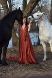 Frau in einem roten langen Kleid mit zwei Pferden stockfotos